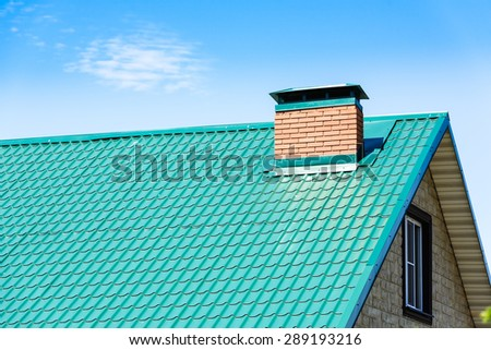 chimney on the roof of the house against the blue sky - stock photo