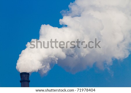 Chimney smoke in the background of blue sky - stock photo