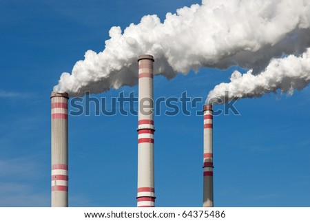 Chimney smoke with blue sky - stock photo