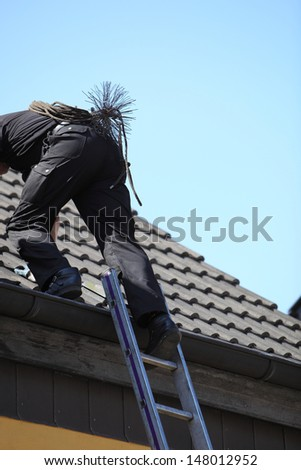 Chimney sweep climbing onto the roof of a house with his wire brush , rope and tools strapped to his back - stock photo