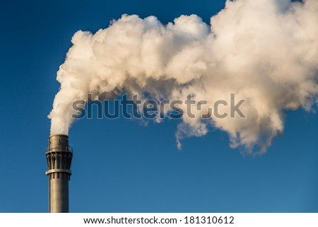 Chimney with white smoke and a blue sky
