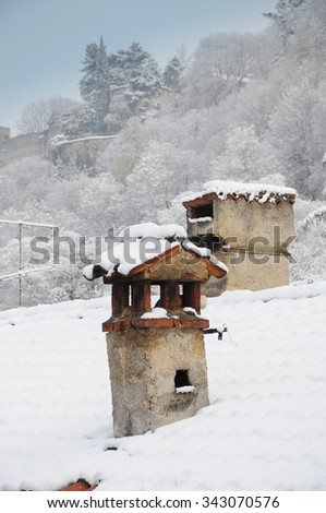 Chimneys covered with snow winter landscape - stock photo