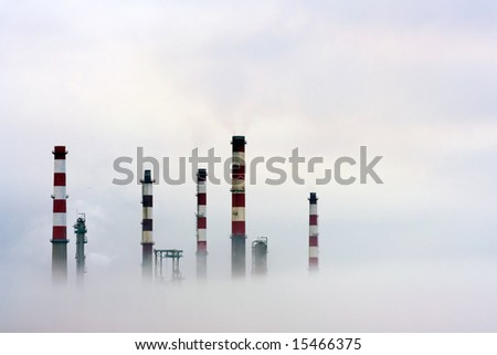 Chimneys of an oil refinery semi lost in the fog