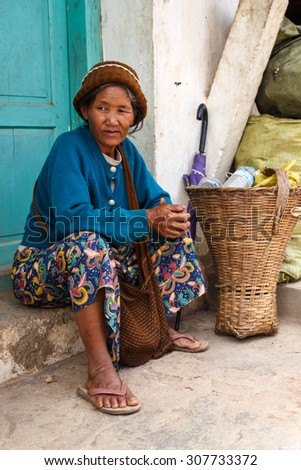 CHIN STATE, MYANMAR - JUNE 18 2015: Older lady sitting on street in the recently opened for tourists Chin State Mountainous Region, Myanmar (Burma) - stock photo
