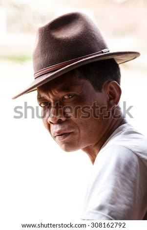 CHIN STATE, MYANMAR - JUNE 18 2015: Smart man in hat, sitting in the recently opened for tourists Chin State Mountainous Region, Myanmar (Burma) - stock photo