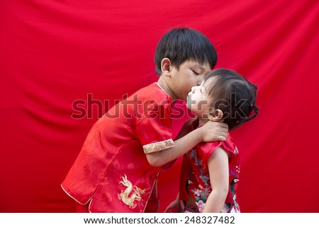China boy and girl  in traditional Chinese red Tang suit greeting - stock photo