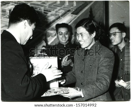 CHINA - CIRCA 1958: Chinese girl gives a souvenir to member of the Soviet delegation Chinese People's Republic, 1958