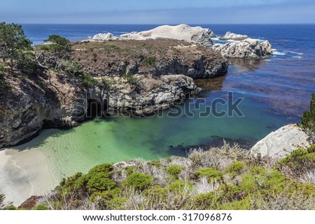 China Cove / Beach in Point Lobos State Natural Reserve, with emerald green waters & rock formations along the rugged Big Sur coastline, near Carmel and Monterey, CA. on the California Central Coast. - stock photo