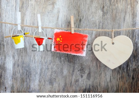 China flag paint brushes clothespin rope vintage wooden background - stock photo