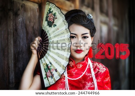 China Girl , Chinese Calligraphy 2015 Year of the Goat 2015,Chinese woman red dress traditional cheongsam ,close up portrait with old wood door - stock photo