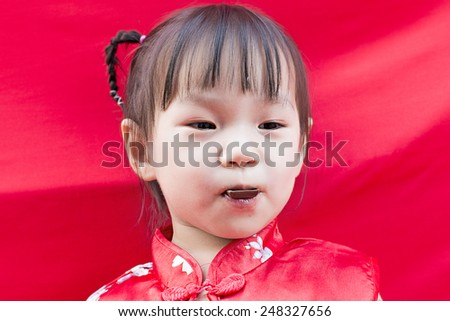 China girl in traditional Chinese red Tang suit greeting - stock photo