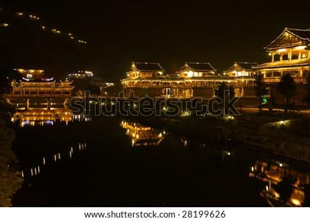china/guizhou: night view of ancient wind-rain bridge in Xijiang Hmong village - stock photo