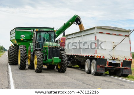 CHINA, MI, USA / July 17, 2016: A tractor pulled grain cart transfers wheat to a semi truck along a China, MI road on July 17, 2016. China is in St Clair County, MI which is a rural area.