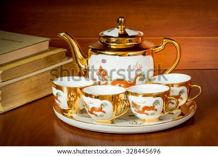 China porcelain Tea set pot and cups with ancient books - stock photo