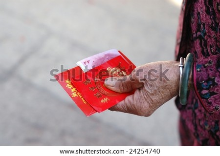 China red packets in an old woman hand, in Chinese new year, the old man will put some money in the red packets, and give it to young boy & girl, to wish them happiness in the new year. - stock photo