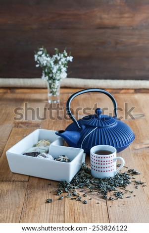 China teapot with flowers and pastels on old wooden table