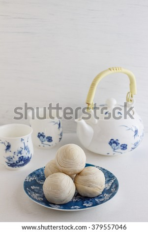 Chinese ancient dessert called 'Pia' or Mung bean filling cake, Chinese pastry or moon cake on dish and teapot set, Traditional delicious cake in asia. - stock photo