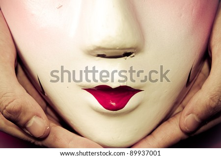 Chinese ancient opera mask in hand - stock photo