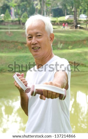 chinese Asian senior man healthy lifestyle working out on a park with a dumbbell