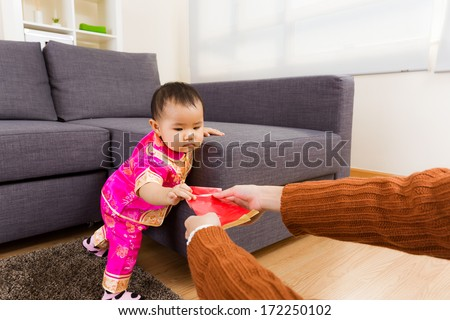 Chinese baby taking red pocket from adult - stock photo
