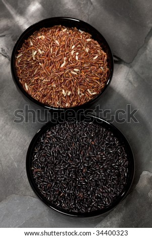 chinese black and Himalayan red long grain Rice in black bowls on stone backdrop, shallow DOF,focus on the first bowl. - stock photo