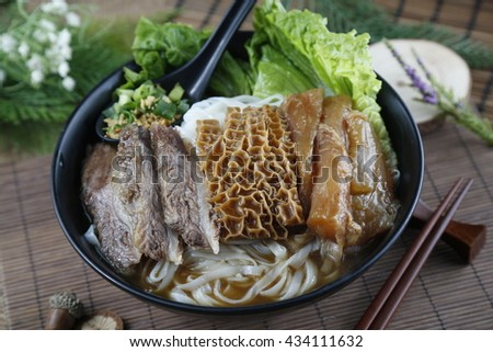 Chinese bowl of vermicelli noodle with fried beef, cow's stomach and salad on the table - stock photo