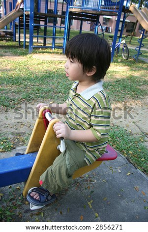 Chinese boy sitting on the seesaw at the children playground - stock photo