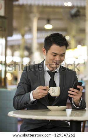 Chinese business man drinking a cup of coffee while sitting with his phone in an Asian food court or Hawker centre cafe. - stock photo