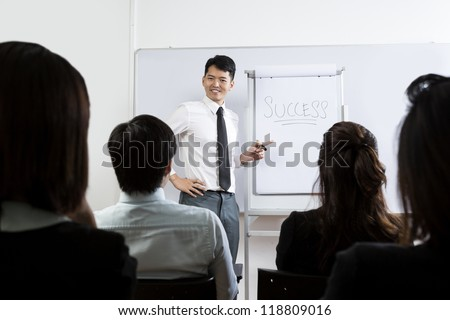 Chinese Business man giving a presentation about success. - stock photo