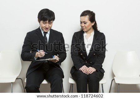 Chinese business man interviewing a female applicant. - stock photo