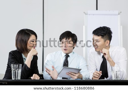 Chinese Business man leading a meeting in the office. - stock photo