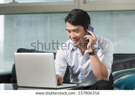 Chinese business man talking on a mobile phone and working on his laptop - stock photo