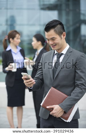 Chinese business Man using his cell phone outdoors in modern Asian city. - stock photo