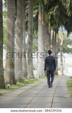 Chinese Business man walking down the street with his back to camera - stock photo