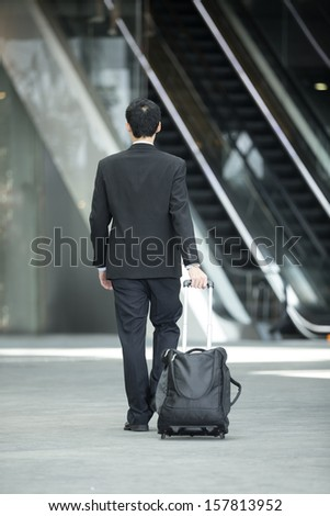 Chinese Business man Walking with a wheeled in modern Asian City