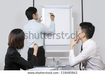 Chinese Business team discussing ideas and writing them on whiteboard. - stock photo