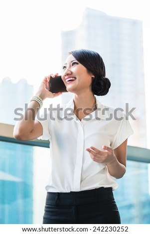 Chinese business woman using phone on terrace in front of city skyline - stock photo