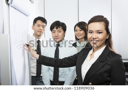Chinese business woman writing 'Success' on a Flip Chart with her team around her. - stock photo