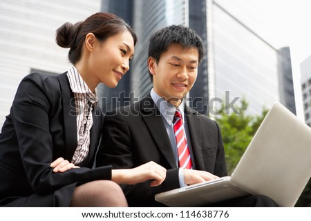 Chinese Businessman And Businesswoman Working On Laptop Outside Office - stock photo