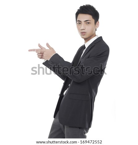 Chinese businessman attire pointing his hand - stock photo