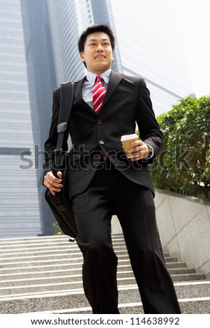 Chinese Businessman Rushing Down Steps Carrying Bag And Takeaway Coffee - stock photo