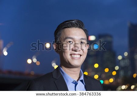 Chinese businessman standing outdoors at night and looking at city skyscrapers. Working late and business on the move concepts. - stock photo