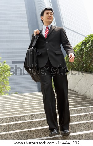 Chinese Businessman Walking Down Steps Carrying Bag Outside Office - stock photo