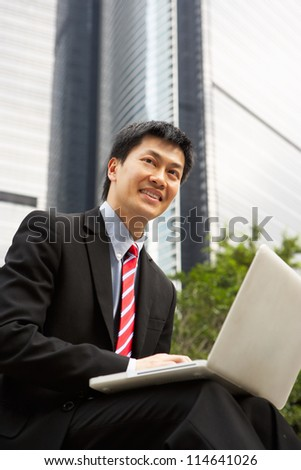 Chinese Businessman Working On Laptop Outside Office - stock photo