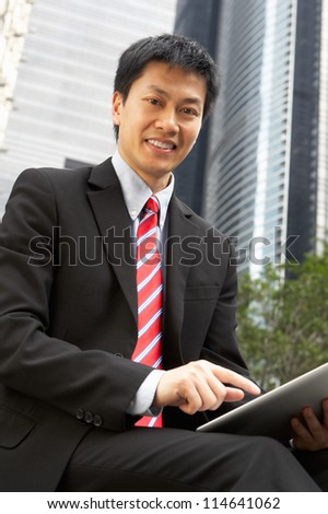 Chinese Businessman Working On Tablet Computer Outside Office - stock photo