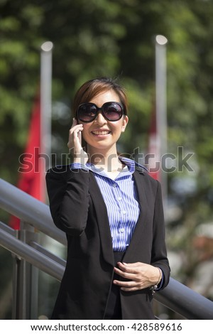 Chinese businesswoman with a Smart Phone looking away standing in front of flags.