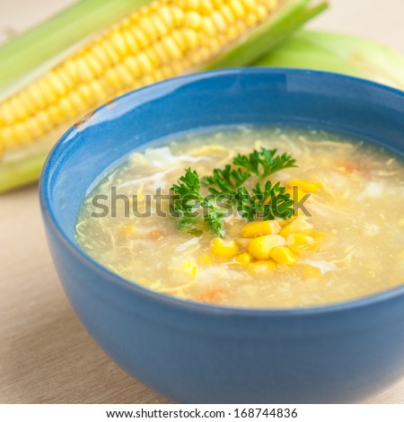 Chinese chicken and corn soup with fresh corn cob on the side.