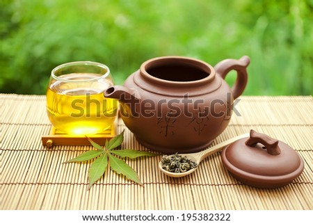 Chinese clay teapot, glass cup and wooden spoon with green tea  - stock photo
