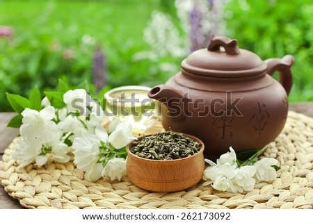 Chinese clay teapot with glass cup, green tea and jasmine flower - stock photo