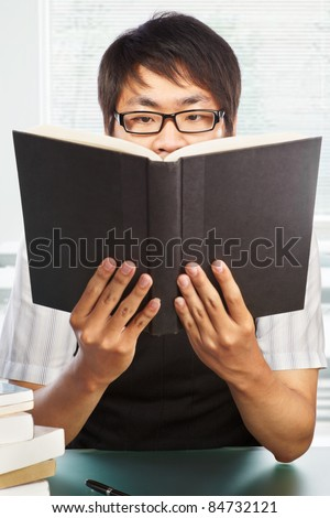Chinese college male student holding up his book high - stock photo